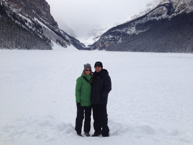 couple standing on a frozen lake louise
