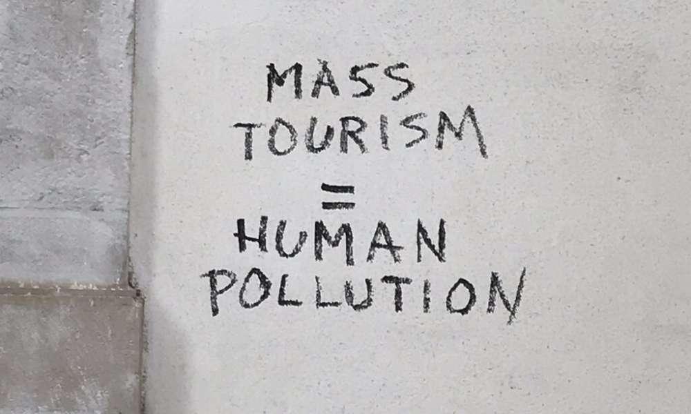 overtourism: mass tourism equals human pollution graffiti
