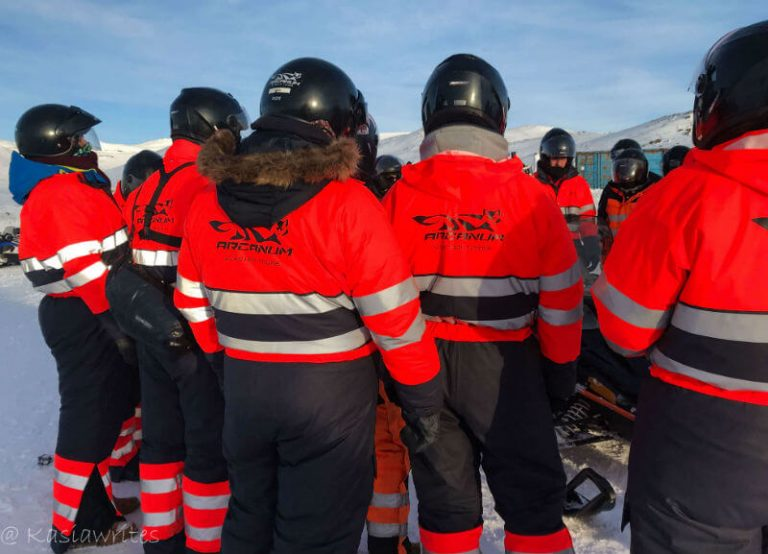 a group of riders in orange snowmobile suits with black helmets