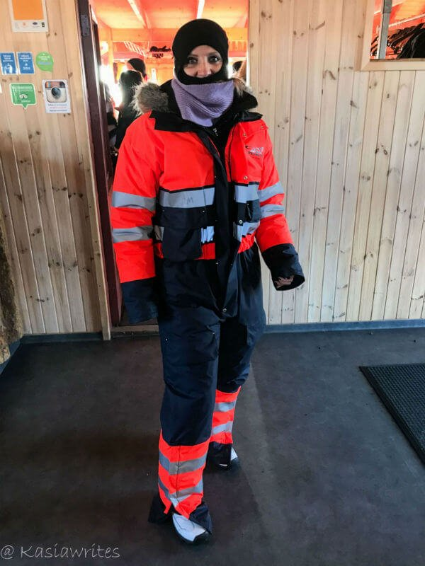 person in an orange snow suit waiting to do a snowmobile tour in Iceland