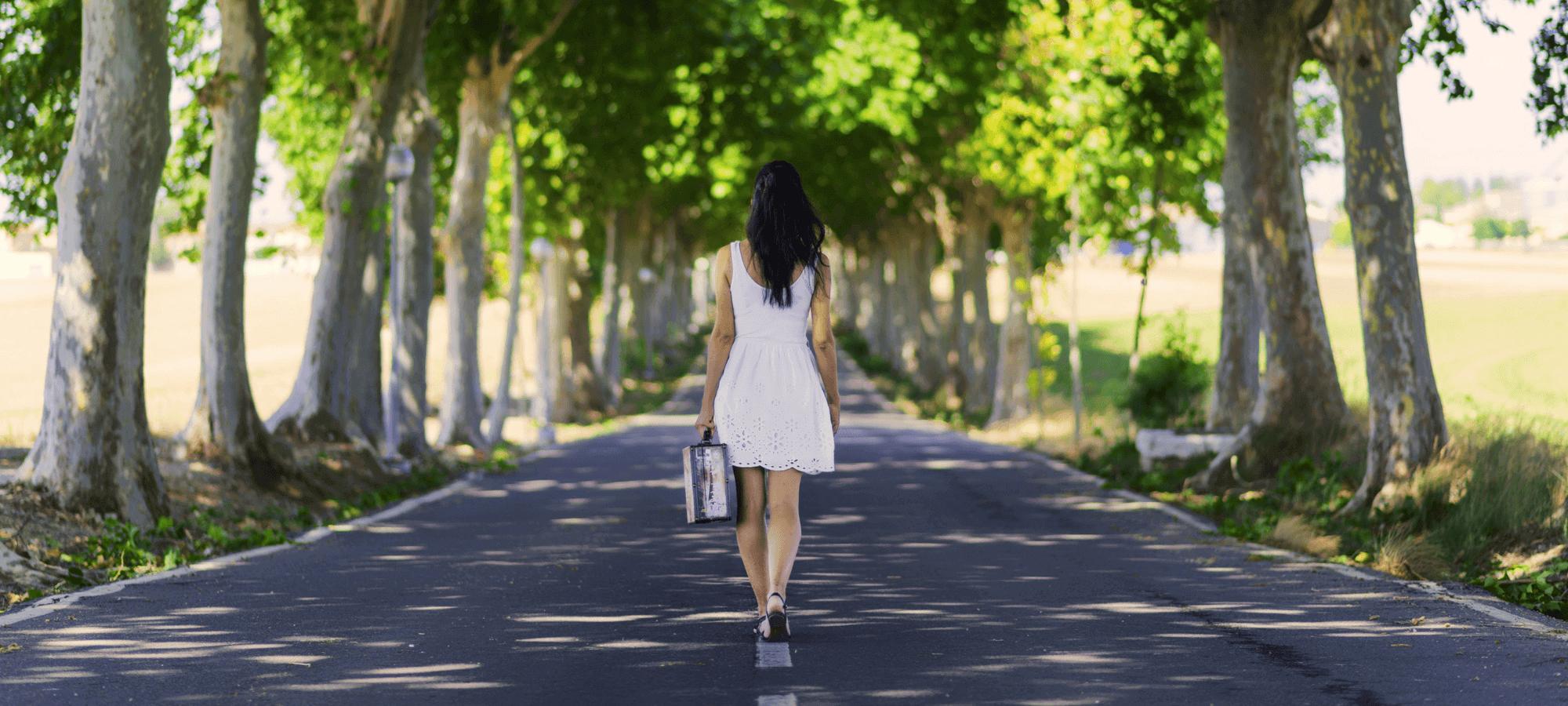 woman walking down a tree lined road