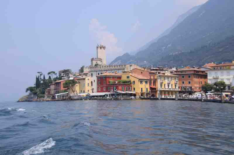 a view of colourful homes and castle tower of Malcesine