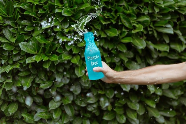hand holding a blue plastic free bottle