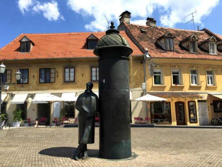 statue leaning against metal poster pole on Vlaska street