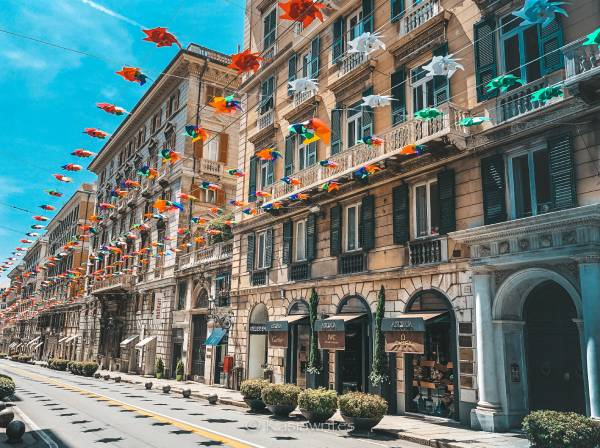 street decorated with hanging flags in Genoa