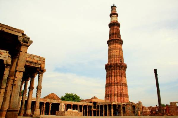 brick tower of Qutub Minar and surrounding structures in Delhi