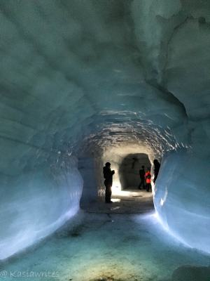 person standing at the back of a blue ice cave