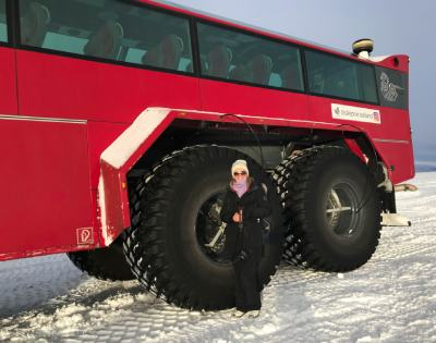standing beside a giant tire of a bus on lave and ice caves tour