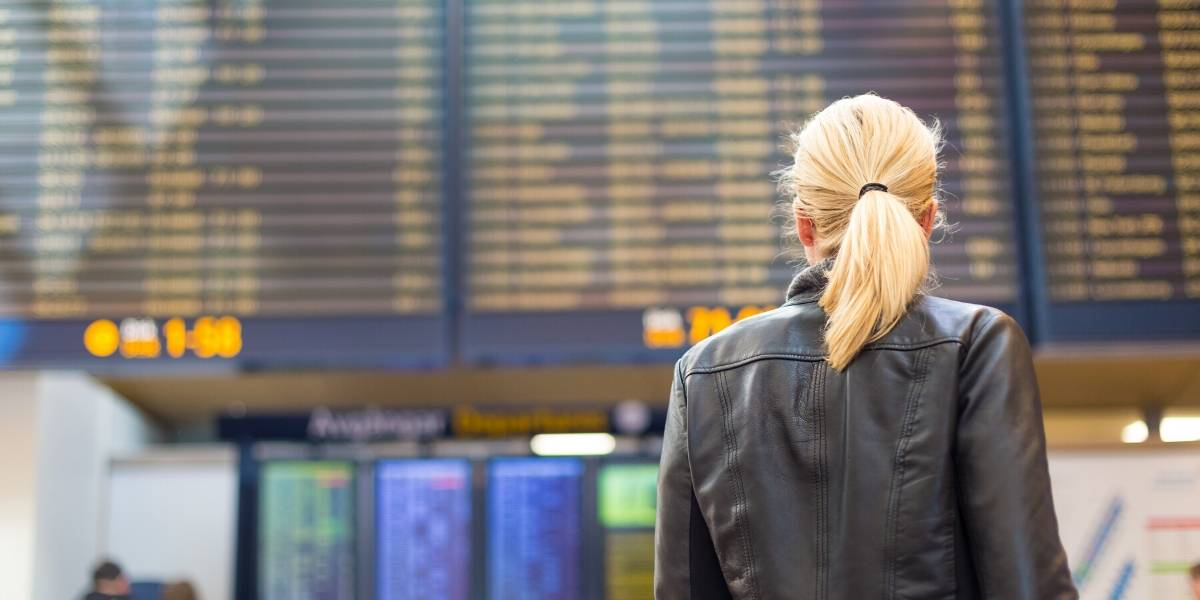 woman looking up at flight schedule board