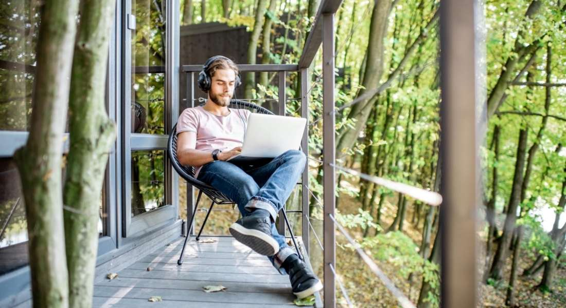 digital nomad visa - man working on laptop while sitting on a balcony in the forest