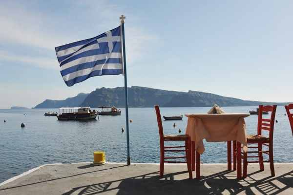 Greek flag on a pier beside a table