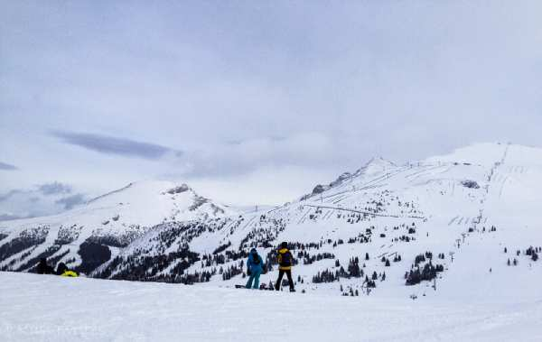 snowboarders overlooking snowy mountains