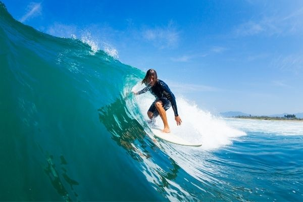 man riding the wave on a surfboard