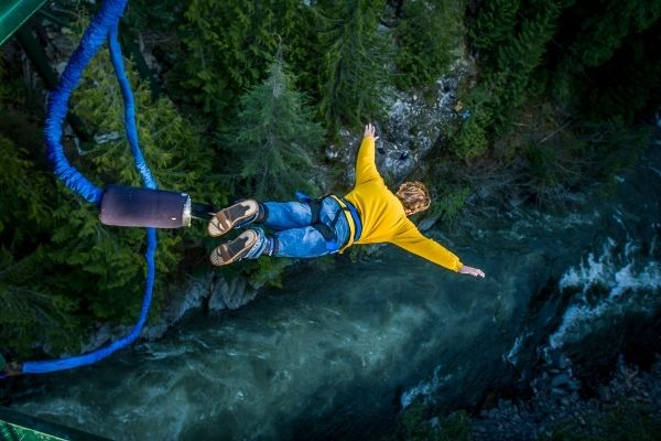 A person wearing a yellow shirt and blue pants is jumping over water while attached to a rope