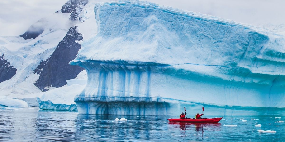 couple kayaking in front of a glacier