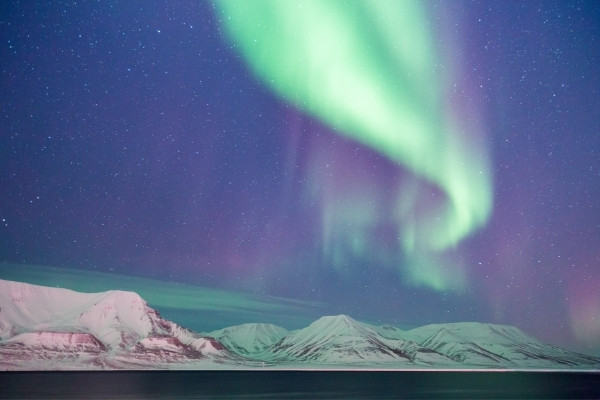 Norther Lights over snow-covered peaks in norway
